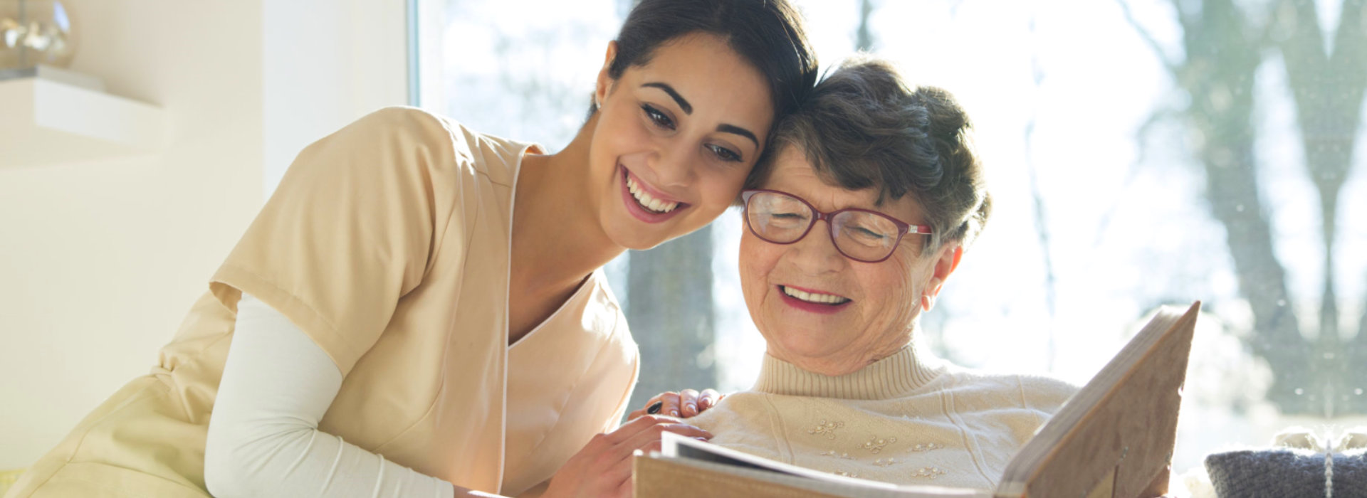 senior woman and caregiver looking at a photo album